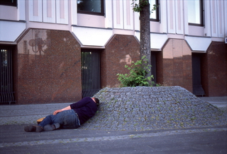 "Drunk, 35mm Color Negative, 2011  Steamy mid summer nap in reach of the ""Bonner Loch"" - a hot spot for the local down and outs who are facing the loss of their habitat following the latest announcements by the city council of Bonn and privat investment groups  in 2014 in an desperate attempt to clean up the centre of the city once and for all."
